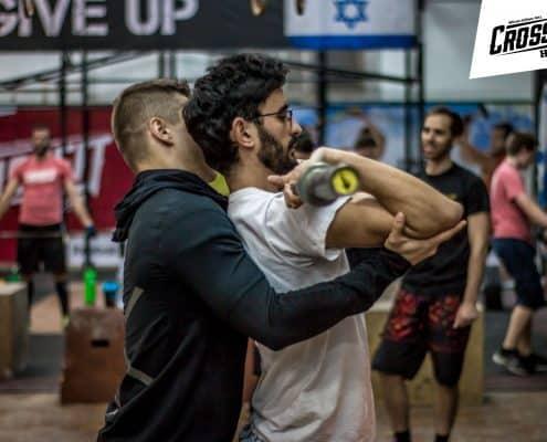המאמן אנטון מתקן טכניקה למתאמן בתרגיל הפרונט סקוואט בקרוספיט חיפה